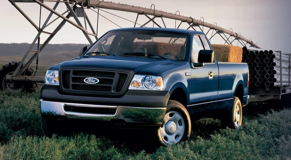 A blue 2006 used Ford-F-150 is hauling a trailer full of pipes.