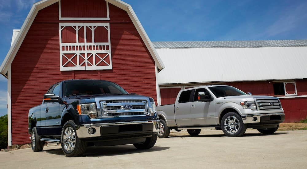 A dark blue and a silver 2014 used Ford F-150 Ranger XLT Lariat are parked in front of a red and white barn.
