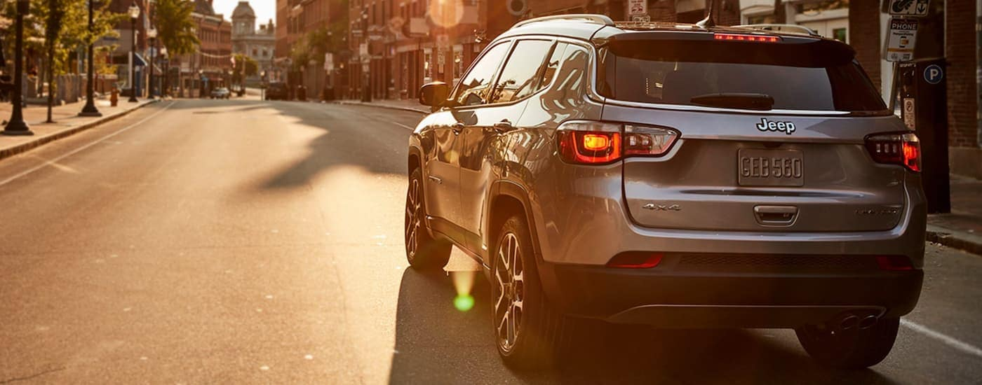 A silver 2021 Jeep Compass is driving on an empty city street at sunrise.