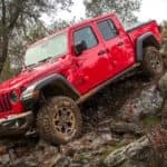 A red 2021 Jeep Gladiator with hard top is climbing over rocks after winning the 2021 Jeep Gladiator vs 2021 Ford Ranger comparison.