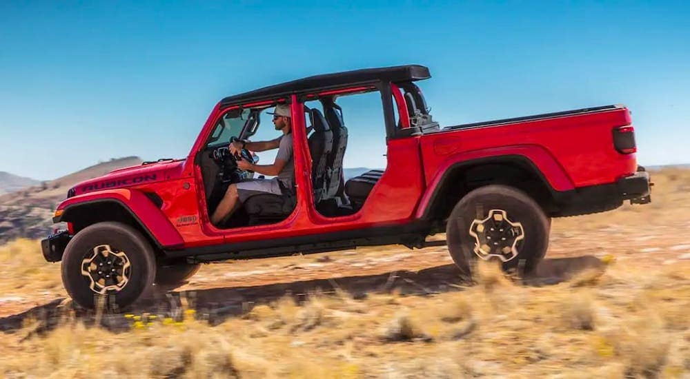 A red 2021 Jeep Gladiator Rubicon with no doors is shown from the side driving in a field.