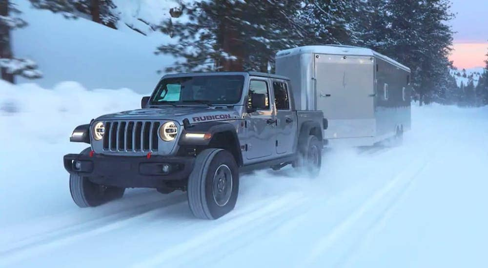 A silver 2021 Jeep Gladiator Rubicon is driving on a snowy road and towing an enclosed trailer.