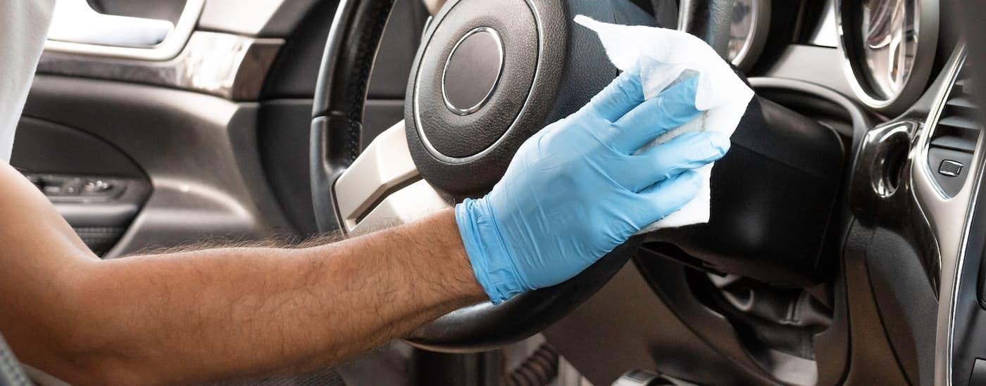 A gloved hand is wiping down the steering wheel in.a vehicle.
