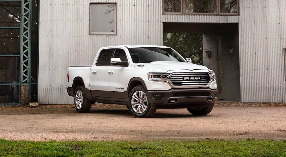 A white 2019 Ram 1500 diesel is parked in front of a metal building.
