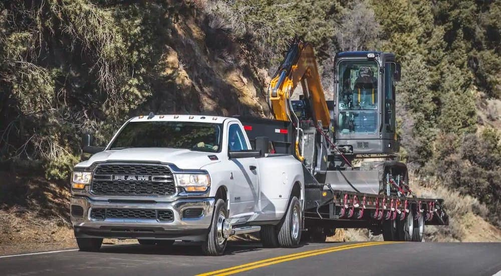A popular used diesel truck in Colorado Springs, a white 2019 Ram 3500 diesel, is towing construction equipment on a highway.