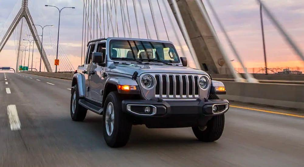 A silver 2019 Jeep Wrangler Unlimited is driving over a bridge at dusk after leaving a used Jeep dealer near you.