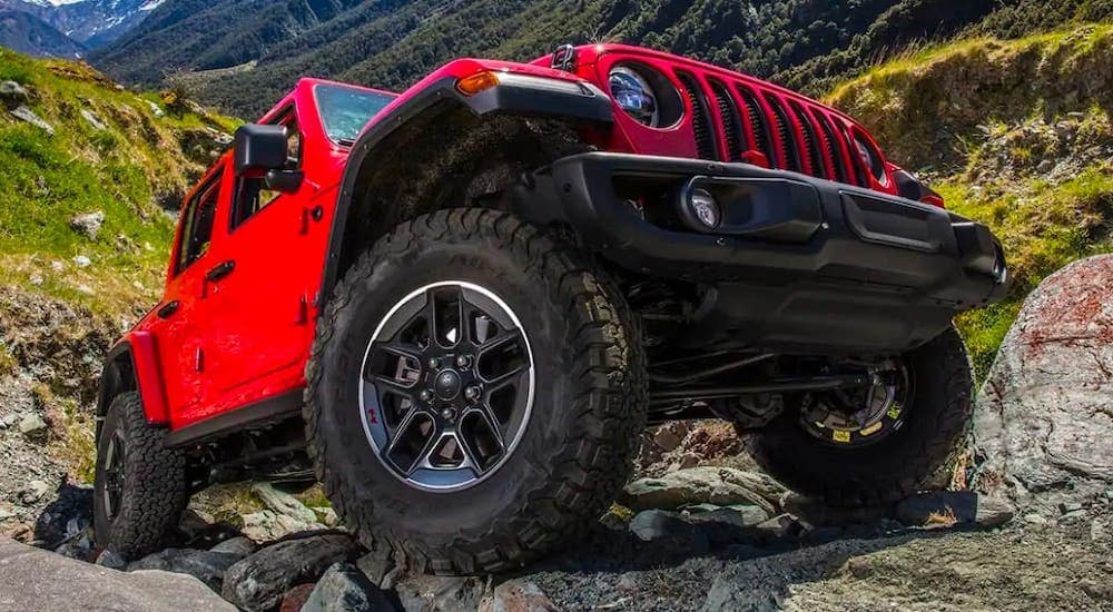 A red 2019 Jeep Wrangler Unlimited is shown from a low angle climbing over rocks.
