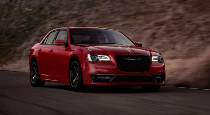 A red 2021 Chrysler 300 is driving on a highway after leaving a Colorado Springs Chrysler dealership.