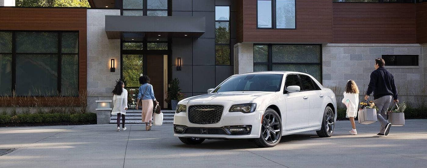 A family is walking away from a white 2021 Chrysler 300 and towards a modern home.