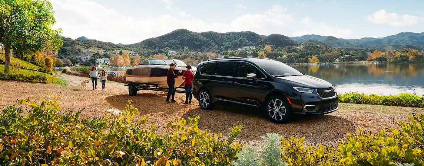 A family is next to a black 2021 Chrysler Pacifica towing a boat in front of a lake.