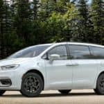 A white 2021 Chrysler Pacifica Hybrid is parked in front of trees.