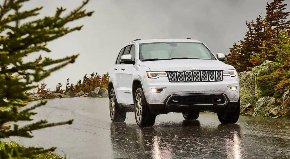 A white 2021 Jeep Cherokee SRT is driving on a wet road after leaving a Jeep dealership in Colorado Springs.