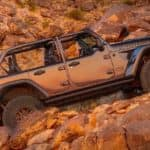 A silver 2021 Jeep Wrangler Rubicon 392 with no roof is shown from the side while climbing on a rocky road.