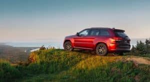 A red 2019 used Jeep Grand Cherokee is parked on a hill overlooking a coast.