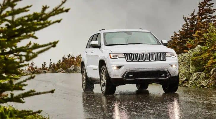 A white 2021 Jeep Grand Cherokee is driving on a wet road after leaving a Black Forest Jeep dealer.