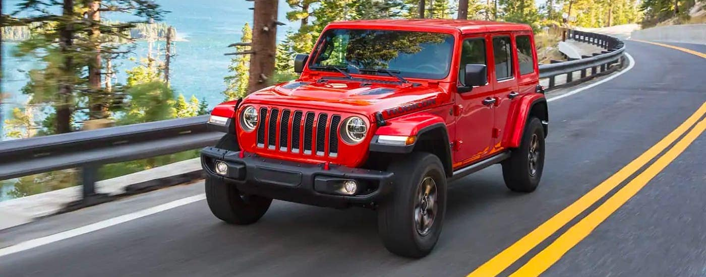 A red 2021 Jeep Wrangler Unlimited is driving on a winding highway.