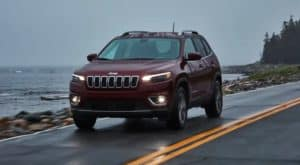 A red 2017 Certified Pre-Owned Jeep Cherokee is driving on a coastal highway in the rain at dusk.