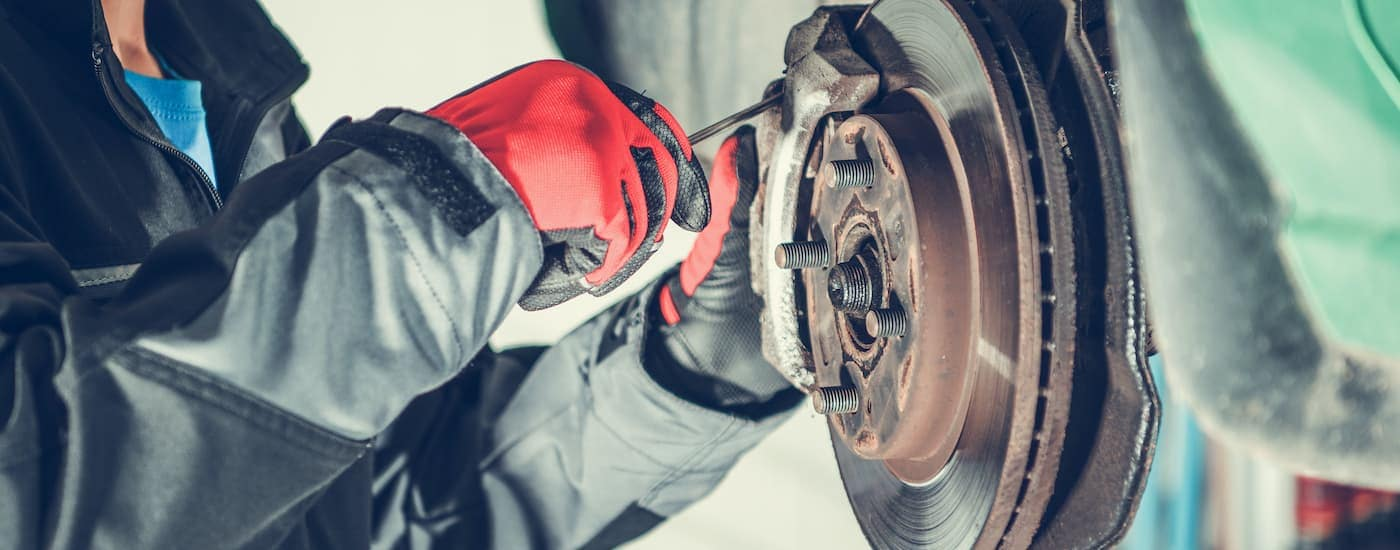 A close up shows gloved hands removing a brake pad from a caliper.