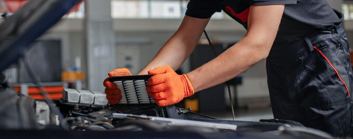 A close up shows a mechanic changing a filter during a Jeep service.