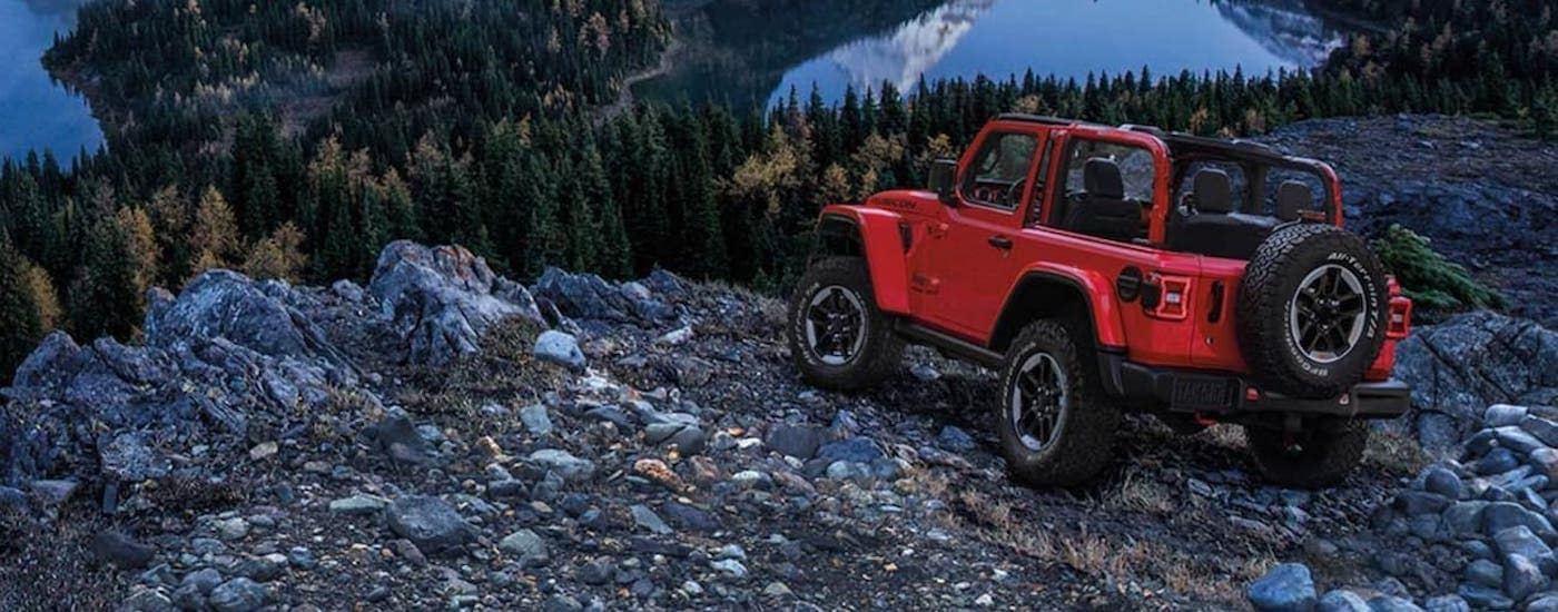 A red 2020 Jeep Wrangler is shown from the rear parked in the mountains after looking at used Jeep Wranglers for sale.