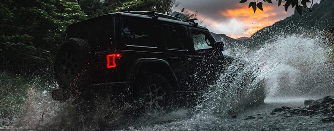 A black 2020 Jeep Wrangler Unlimited is shown driving through a river.