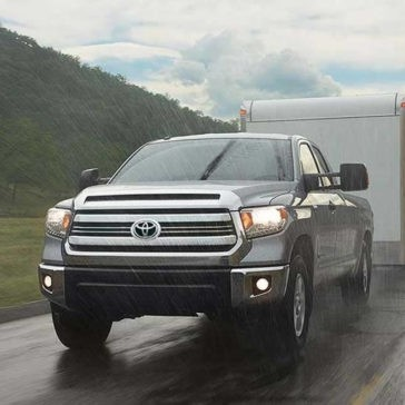 2017 Toyota Tundra driving in the rain pulling a trailer
