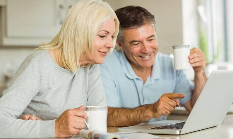 Older Man and Woman Using Computer to Value Their Trade In