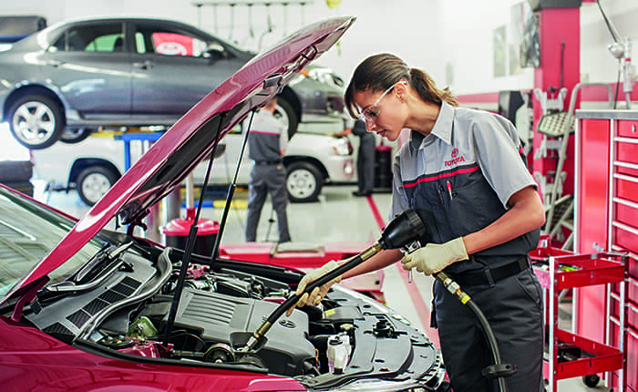 Woman mechanic changing engine oil at Toyota Service Center