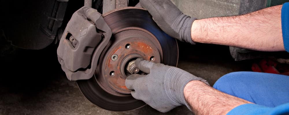 close up of technician working on brake pads