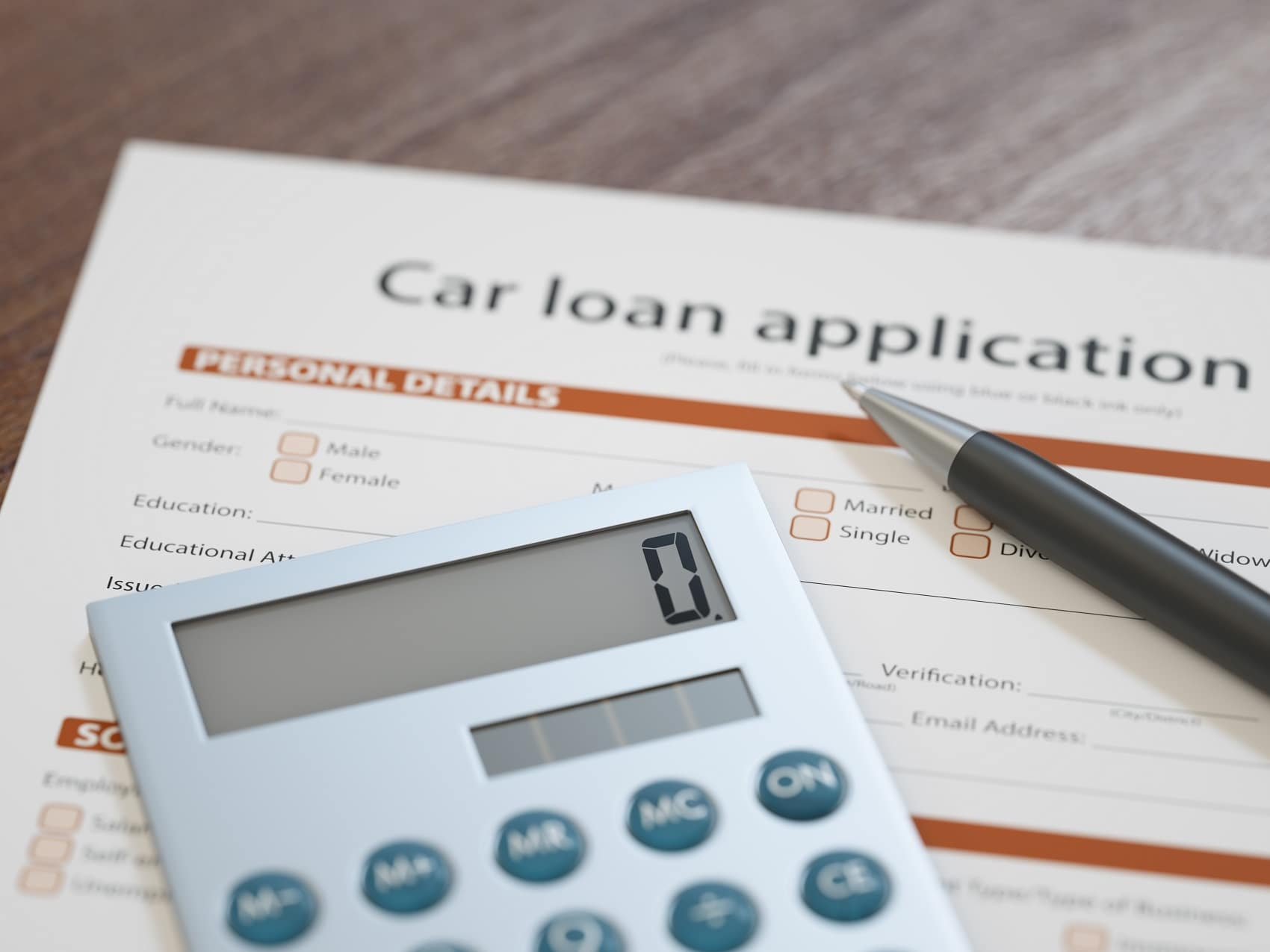 Applying for a car loan close up of calculator and car loan application