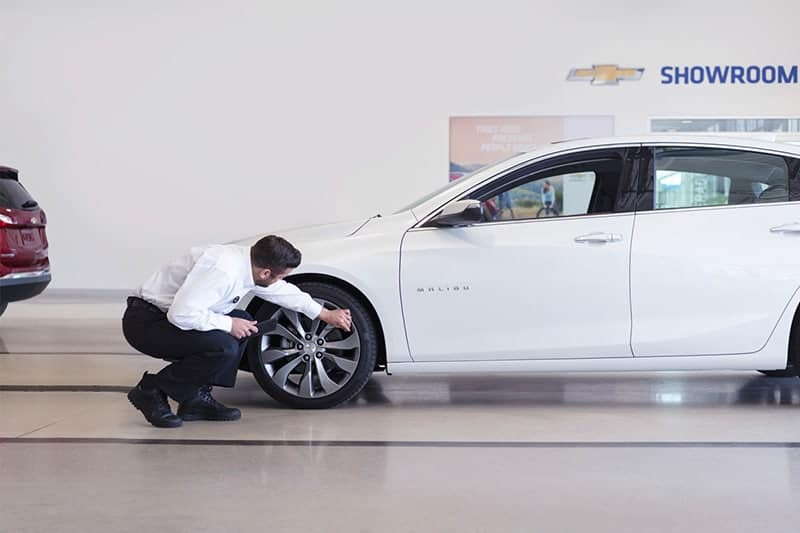 Certified Service Technician checking a vehicle's tire pressure