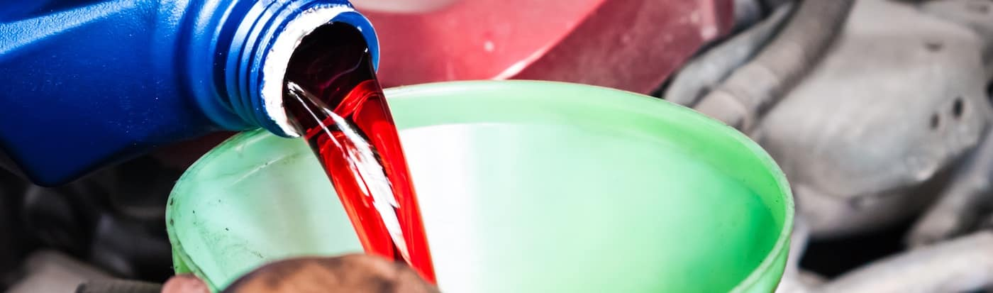 Person pouring transmission fluid into a funnel