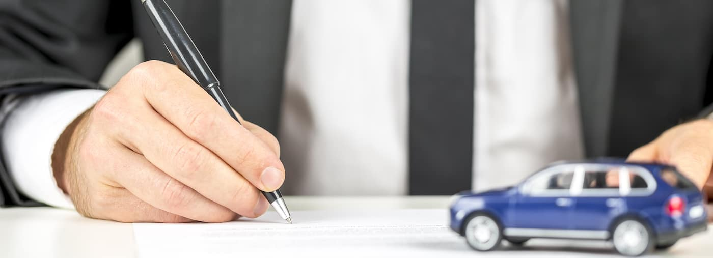 finance paperwork with tiny car