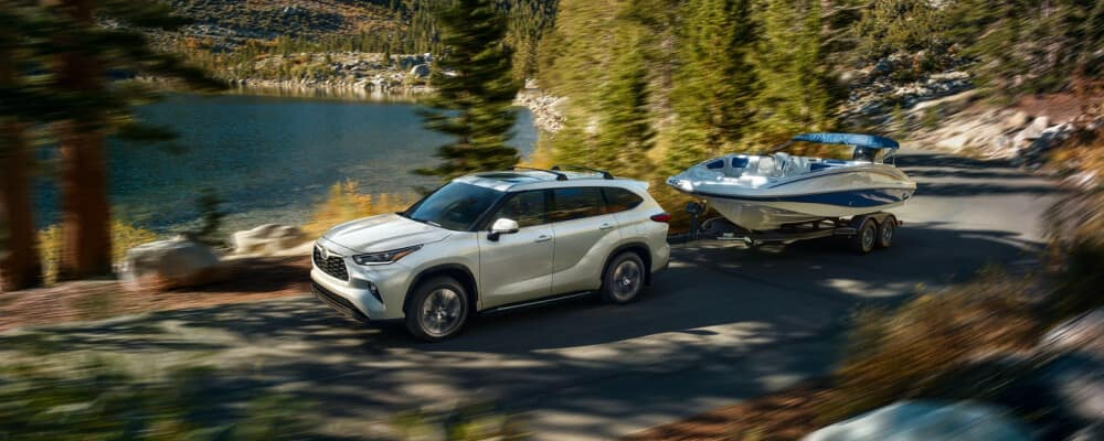 2021 Toyota Highlander towing a boat near the lake
